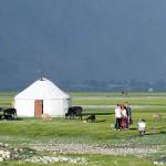 タシュクンガンの牧草地のパオの前で記念写真を撮る中国人