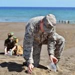 式典後、南海岸で砂を袋に詰める在日米軍司令官のドーラン中将 =19日午後、東京都小笠原村