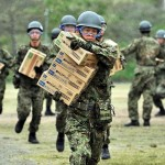 全力疾走で届けられた物資を運ぶ陸自隊員 =23日午後、熊本県南阿蘇村の白水運動公園