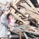倒壊した築100年以上の自宅の前でたたずむ