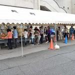 食事の配給を受け取るため並ぶ避難住民ら =25日午後、熊本県の益城町総合体育館