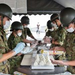 配給のためのおにぎりを第4特科連隊の隊員ら =25日午後、熊本県の益城町総合体育館