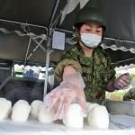 配給のためのおにぎりを握る第4特科連隊の隊員 =25日午後、熊本県の益城町総合体育館