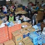救援物資を振り分けるボランティアら =25日午後、熊本県益城町総合体育館