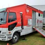 避難所に開設された車両型郵便局。熊本県の職員が業務を行う =25日午後、熊本県益城町総合体育館