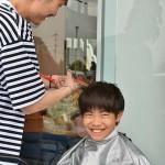 ボランティアに髪を切ってもらいうれしそうな表情を見せる女の子 =25日午後、熊本県益城町総合体育館