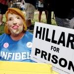 クリントン氏のかぶり物をして、「ヒラリーを監獄に」と書かれたプラカードを掲げる人