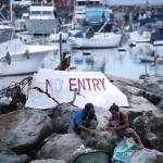 ヨットハーバーを隔てる立ち入り禁止の標識。貧困と裕福の境界線