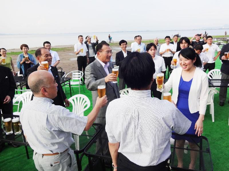 琵琶湖岸でビールやバーベキューを楽しんで