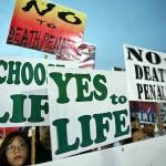 プラカードを掲げて超法規的殺人に反対する若者たち