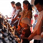 ロウソクを灯し祈りを捧げる信者たち