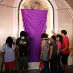 聖母マリアの肖像前で祈りを捧げる人々。グッド・フライデーで肖像画は隠してある