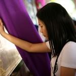 聖母マリアの肖像前で祈る女性