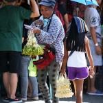 強い日差しのなかサンパギータの花を売る母と娘