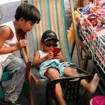 スマホでゲームをしながら店を手伝う子供たち