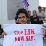 プラカードを掲げ超法規的殺人に反対する女性