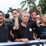 横断幕を広げ行進する左派系団体