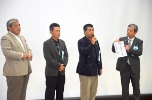 藤田進さん(右)が沖縄の特定失踪者家族3人を紹介した=25日、沖縄県浦添市産業振興センター