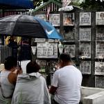 傘をさしながら墓前で故人を偲ぶ家族