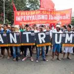 「BAN TRUMP」のプラカードを掲げるデモ隊