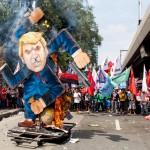 トランプ大統領の肖像に火を放ち気勢を上げるデモ隊
