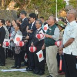 パレード出発式で国歌を歌う参加者=3月27日、沖縄県那覇市緑ヶ丘公園
