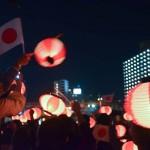 天皇皇后両陛下に向かって提灯を振り、万歳三唱した参加者=3月27日、沖縄県那覇市奥武山公園