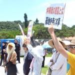 安倍首相の演説中、抗議のプラカードをかかげる人々=23日、沖縄県糸満市の沖縄県平和祈念公園
