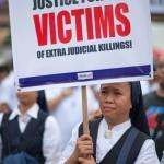 超法規的殺人を非難するプラカードを掲げる女性