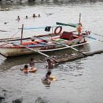 漂着物のゴミで遊ぶ子供たち