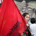 赤い旗を掲げて集会に参加する女性