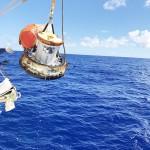 南鳥島沖の海上に着水し、回収船に引き揚げられる小型カプセル=11日午前(JAXA提供)