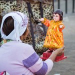 幼少のキリストを模したサントニーニョ像用の着せ替え服を売る女性