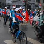 第2回米朝首脳会談の歓迎ムードを盛り上げるために米朝とベトナムの国旗を掲げた自転車でハノイ市内を疾走する若者
