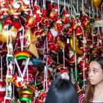 サンタクロースの人形を品定めする買い物客たち