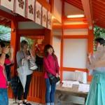 「おもてなし小娘」は外国人と共に、金澤神社の神官から神道について説明を受けた(金沢星稜大学女子短期大学部「おもてなし小娘」提供)