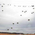 米空軍のC-130Jから降下する陸自の空挺隊員ら =12日午後、千葉県・習志野演習場