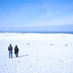 青空の下、まぶしく輝く雪景色の砂丘