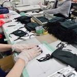 手作業で袋詰めをするエックスデベロップメントのスタッフたち =6日岐阜県岐阜市