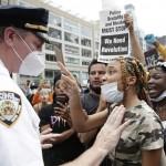 5月28日、米ニューヨークでの抗議デモで白人警官と対立する黒人女性(UPI)