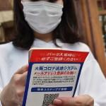 大阪コロナ追跡システム登録のデモンストレーションを行う女性 =4日午前、大阪市此花区