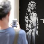 パリ同時テロの現場となったバタクラン劇場の非常口の扉に描かれたバンクシーの作品=2018年6月(AFP時事)