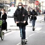 フランス・パリで、封鎖緩和を受けてマスクを着けて自転車やキックボードで移動する住民(5月12日UPI)