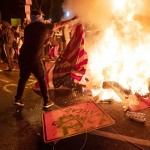 5月31日、ワシントンで、米国旗などを燃やす抗議デモの参加者(AFP時事)