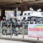 香港返還記念日と「国家安全維持法」成立を祝う横断幕のそばに、デモ隊排除のため集まる警官隊=1日、香港・香港島(時事)