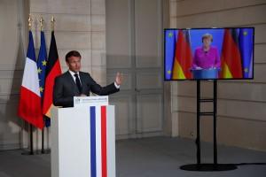 画面を通じて共同記者会見を行うメルケル独首相(右)とマクロン仏大統領(5月18日、パリ、AFP時事)