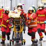 5日、パリのシャルリエブド旧本社付近で、負傷者を運ぶフランスの消防隊(AFP時事)