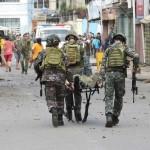 8月24日、フィリピン南部ホロ町で、爆発の負傷者を運ぶ軍人たち(AFP時事)