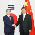 2019年6月27日、大阪市内で、握手する中国の習近平国家主席(右)と韓国の文在寅大統領(EPA時事)