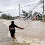 洪水で市中にたまった水に網を投げ魚捕り